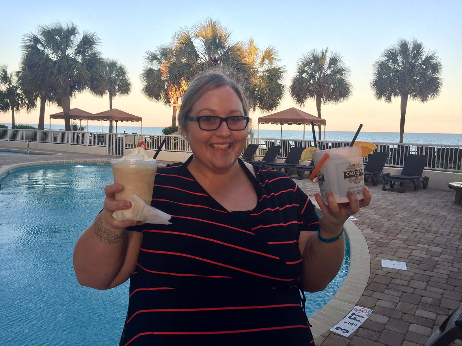 Lady with drinks on pooldeck holding them up