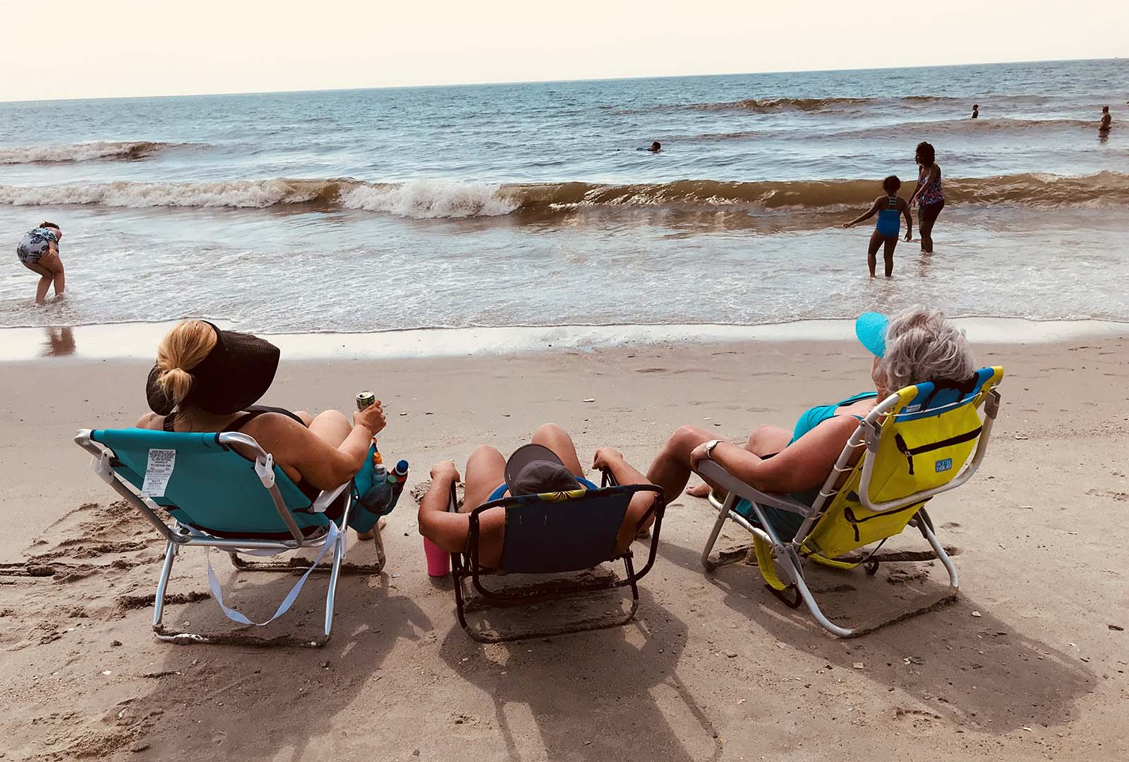 three women sitting in beach chairs by the ocean