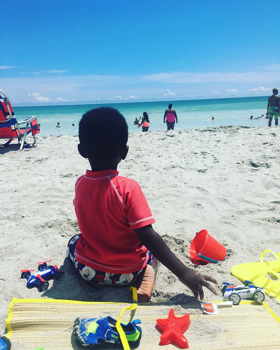 little boy sitting on beach staring at the ocean
