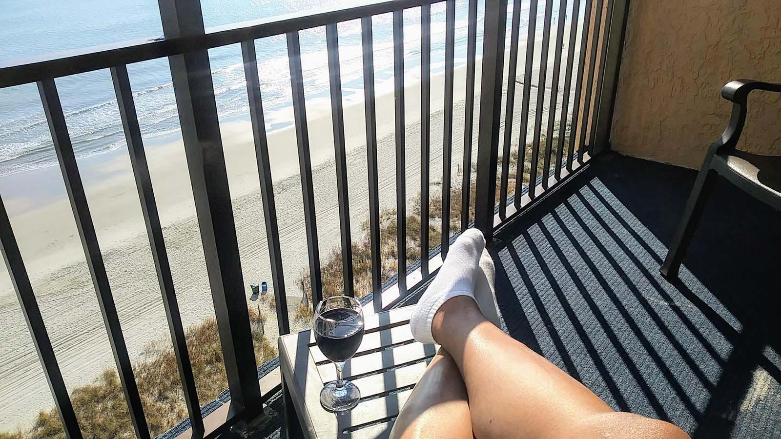 women drinking wine on balcony facing the ocean