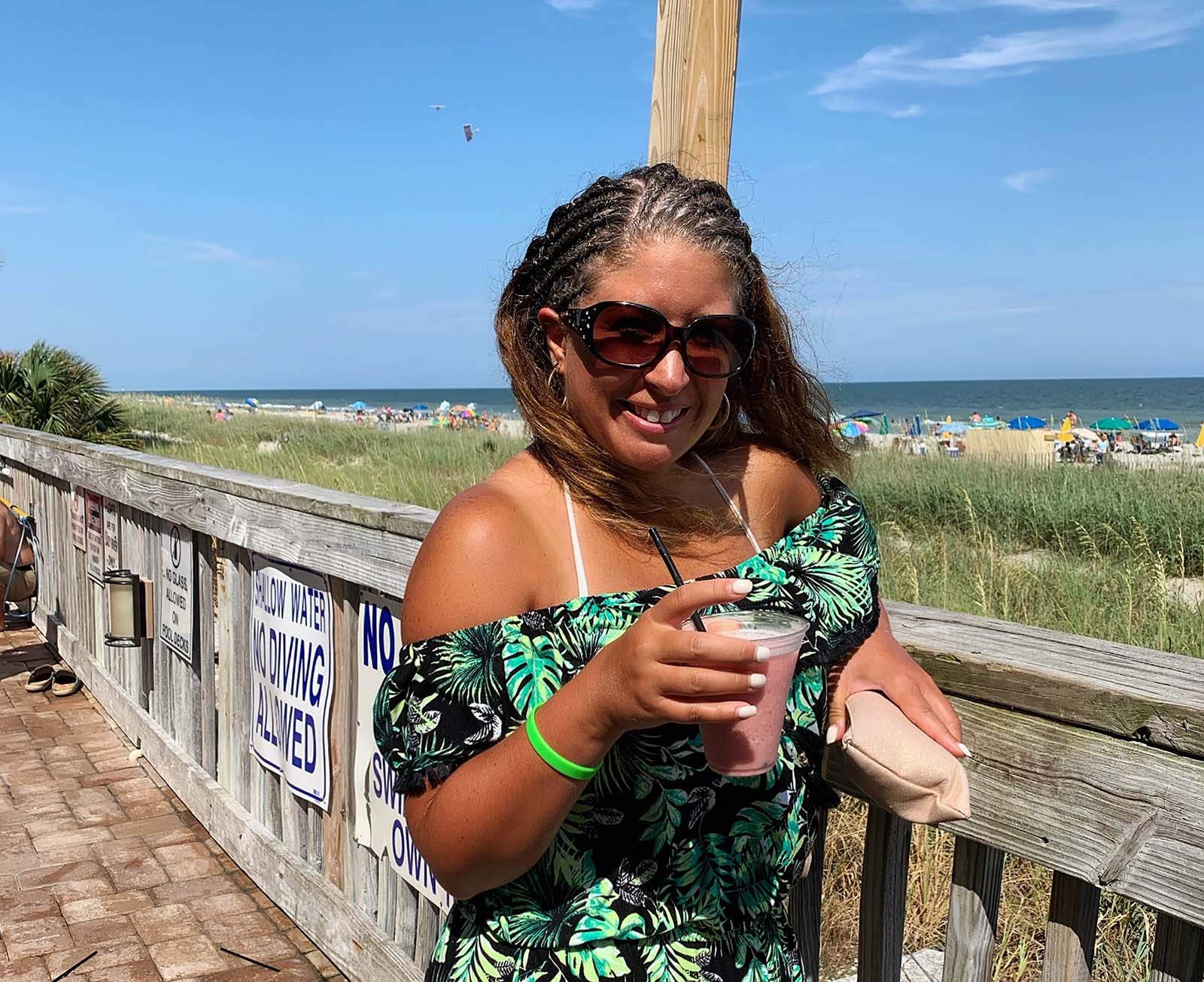 woman posing in front of beach with drink