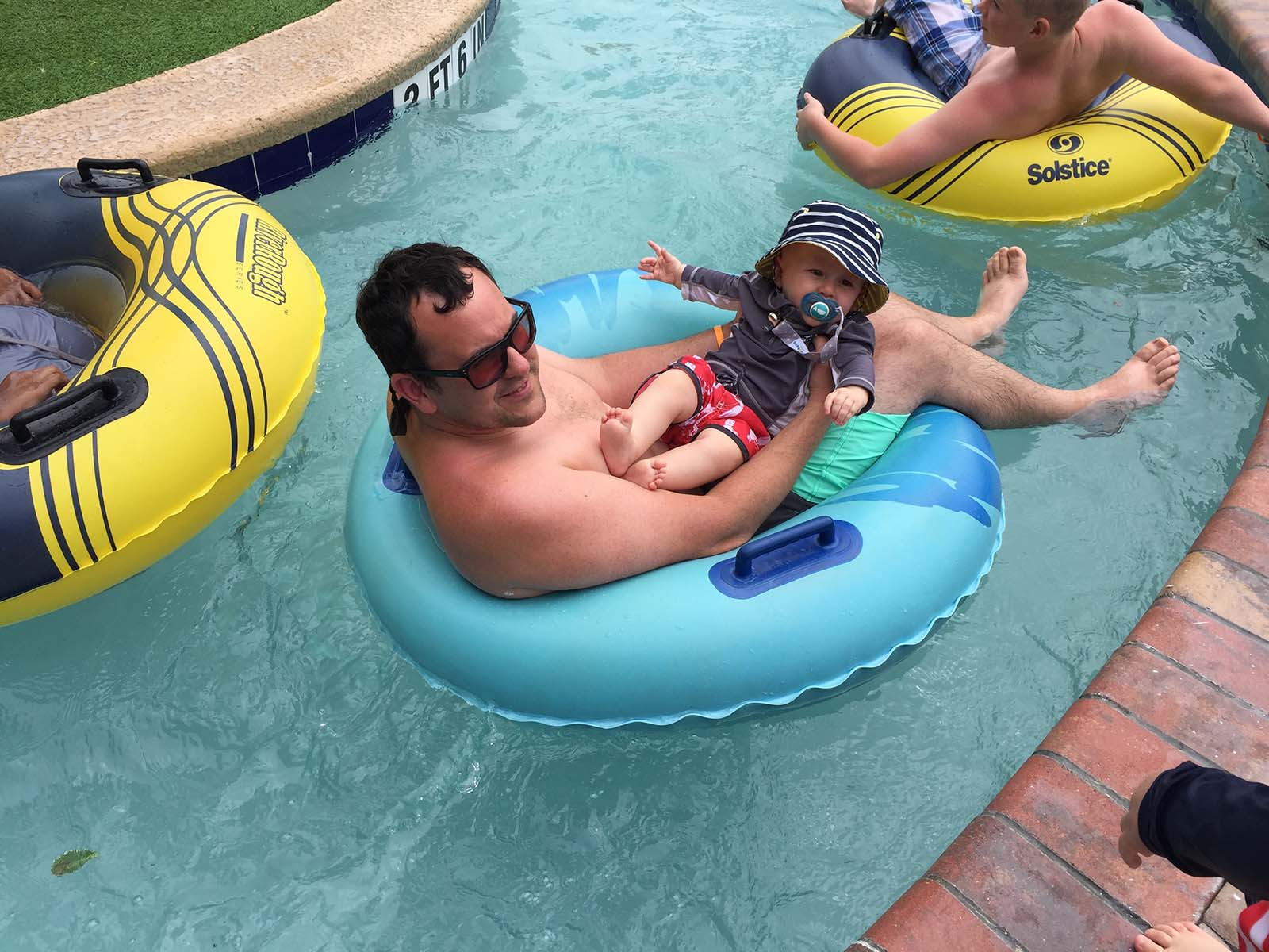Dad holding baby in lap in the lazy river