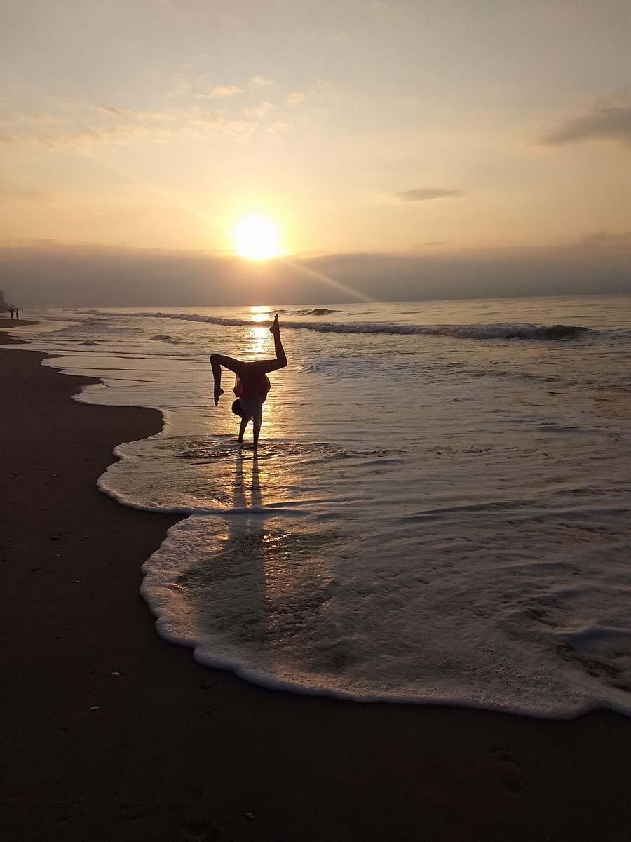 Girl doing yoga on the beach at sunrise
