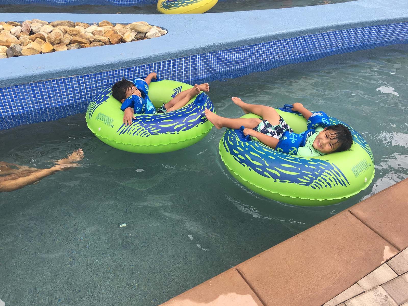 Two boys laying in green tubes in lazy river