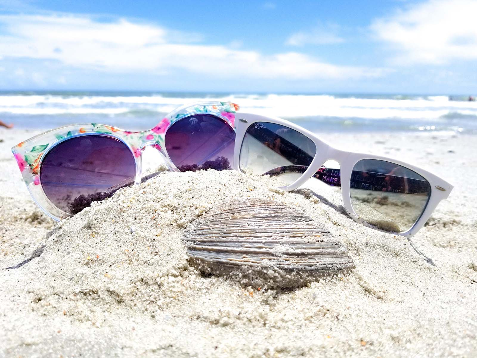 Two sunglasses sitting in sand with seashell