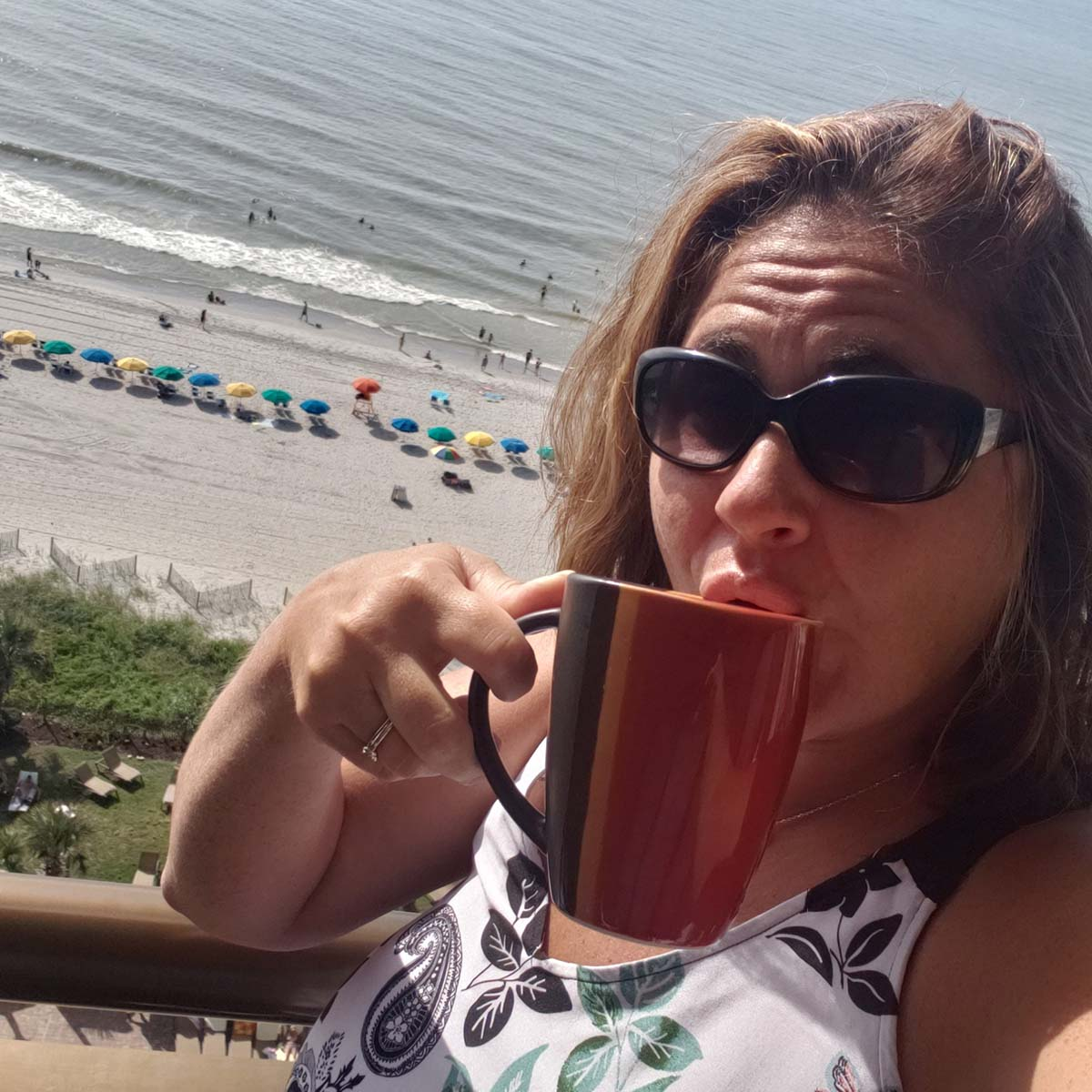 Woman sipping coffee on balcony