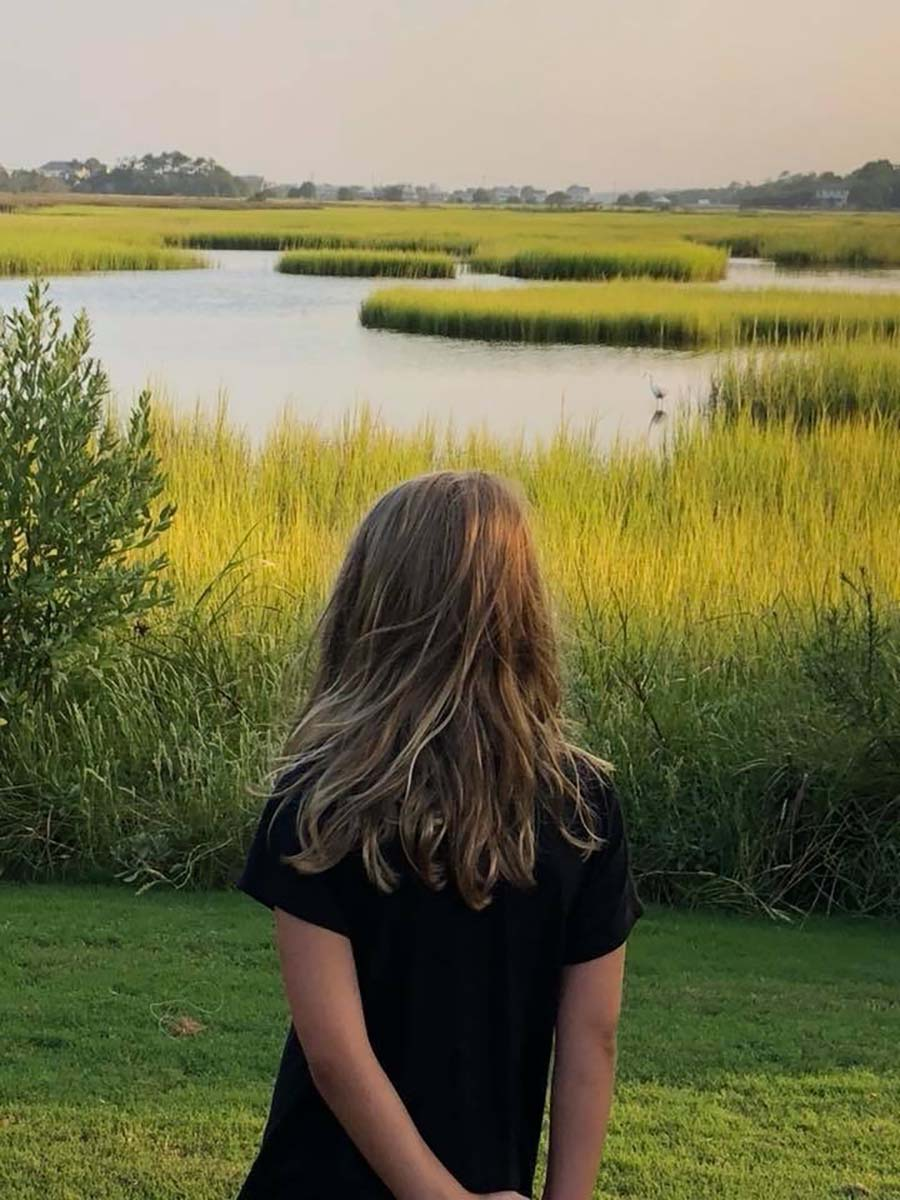 Girl looking into the marsh