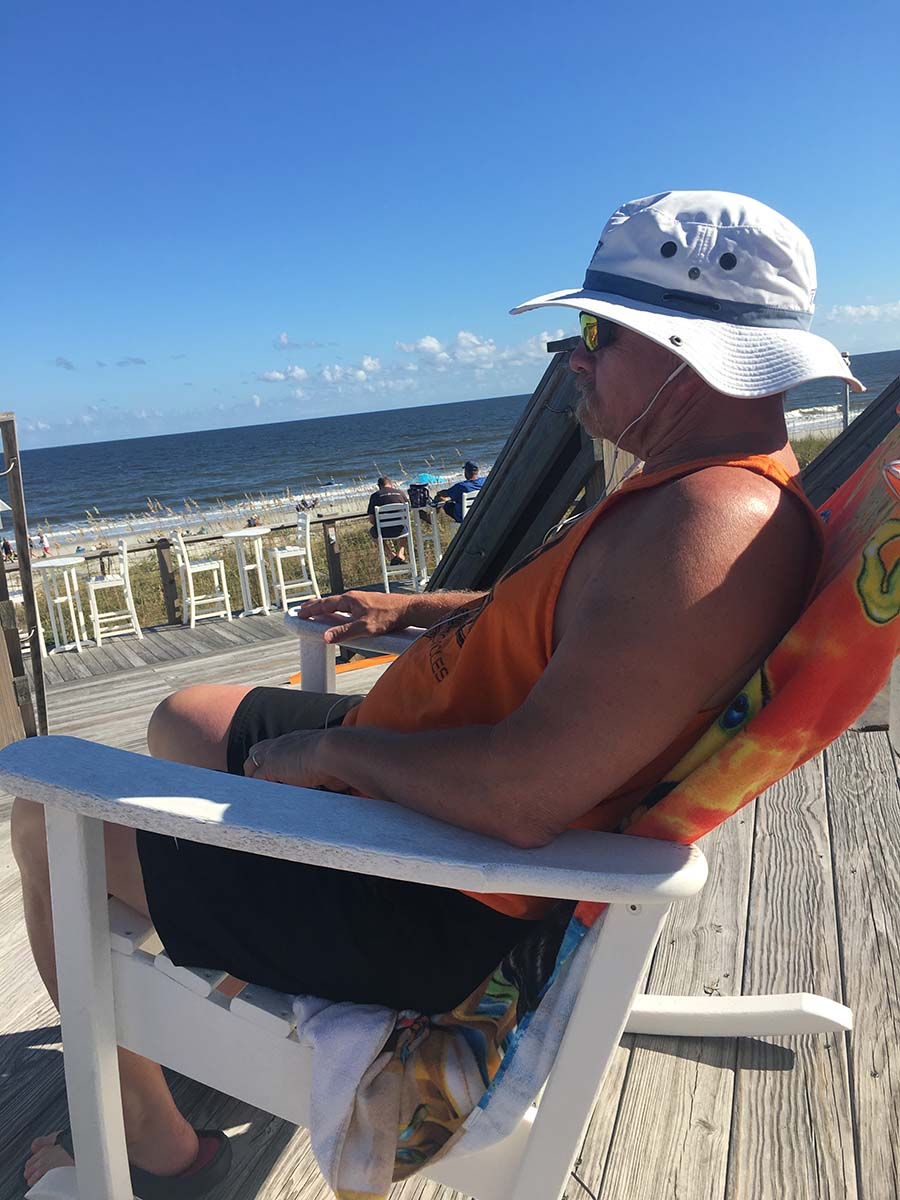 Guy with hat in chair on the beach relaxing