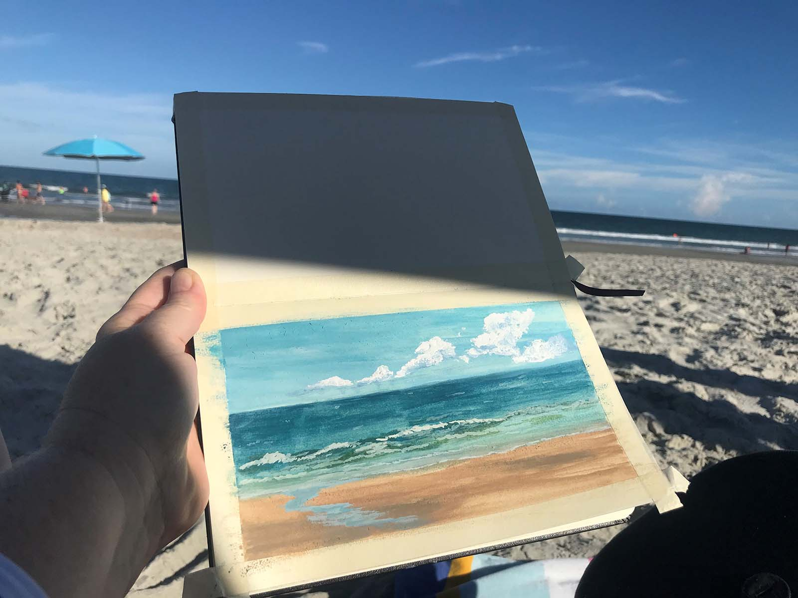 Person painting a blue painting on the beach