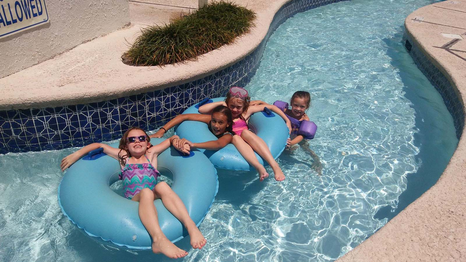 Siblings in lazy river together going down lazy river
