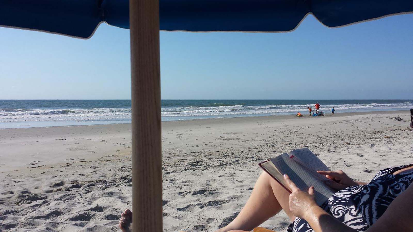 Women on the beach relaxing reading a book
