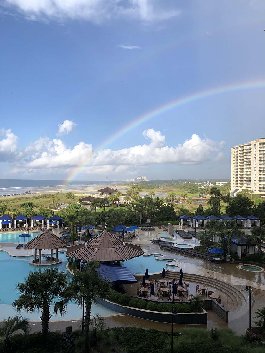 Rainbow in sky over pool