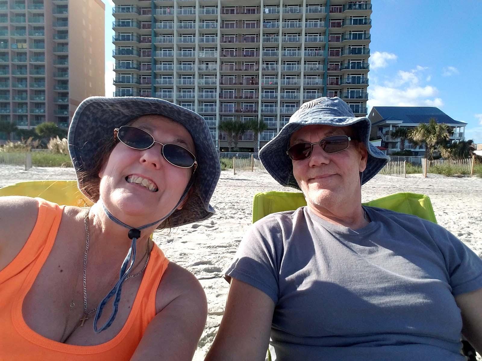 Couple wearing hats on beach taking selfie