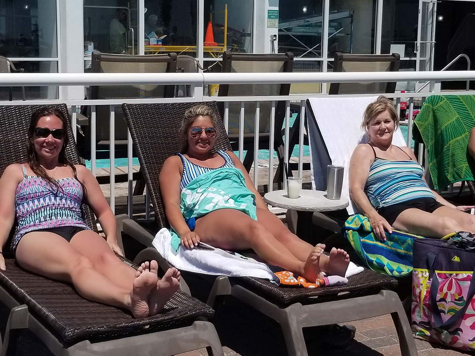 Three girls relaxing in chairs on pooldeck