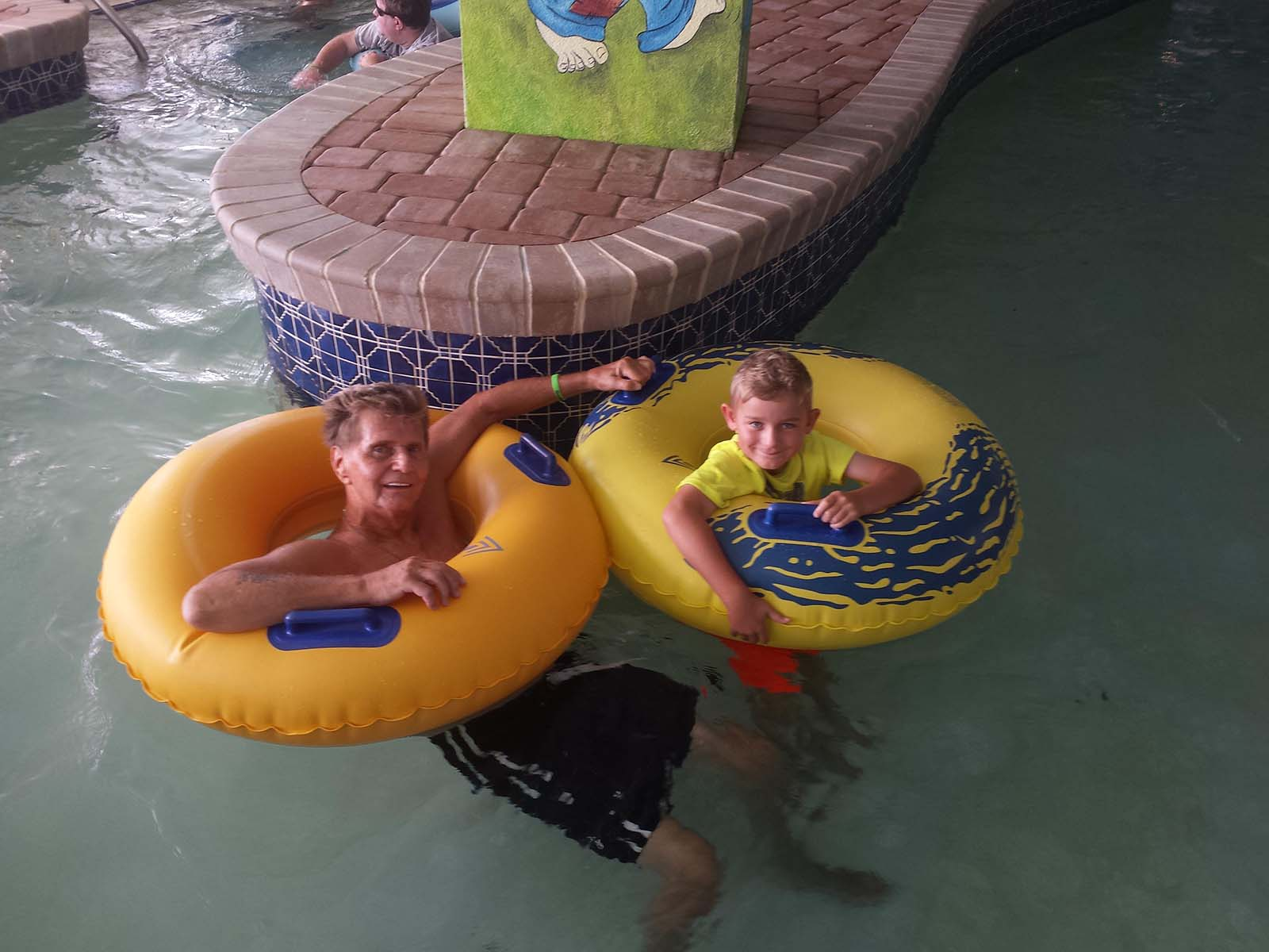 Grandpa and grandkid in lazy river together