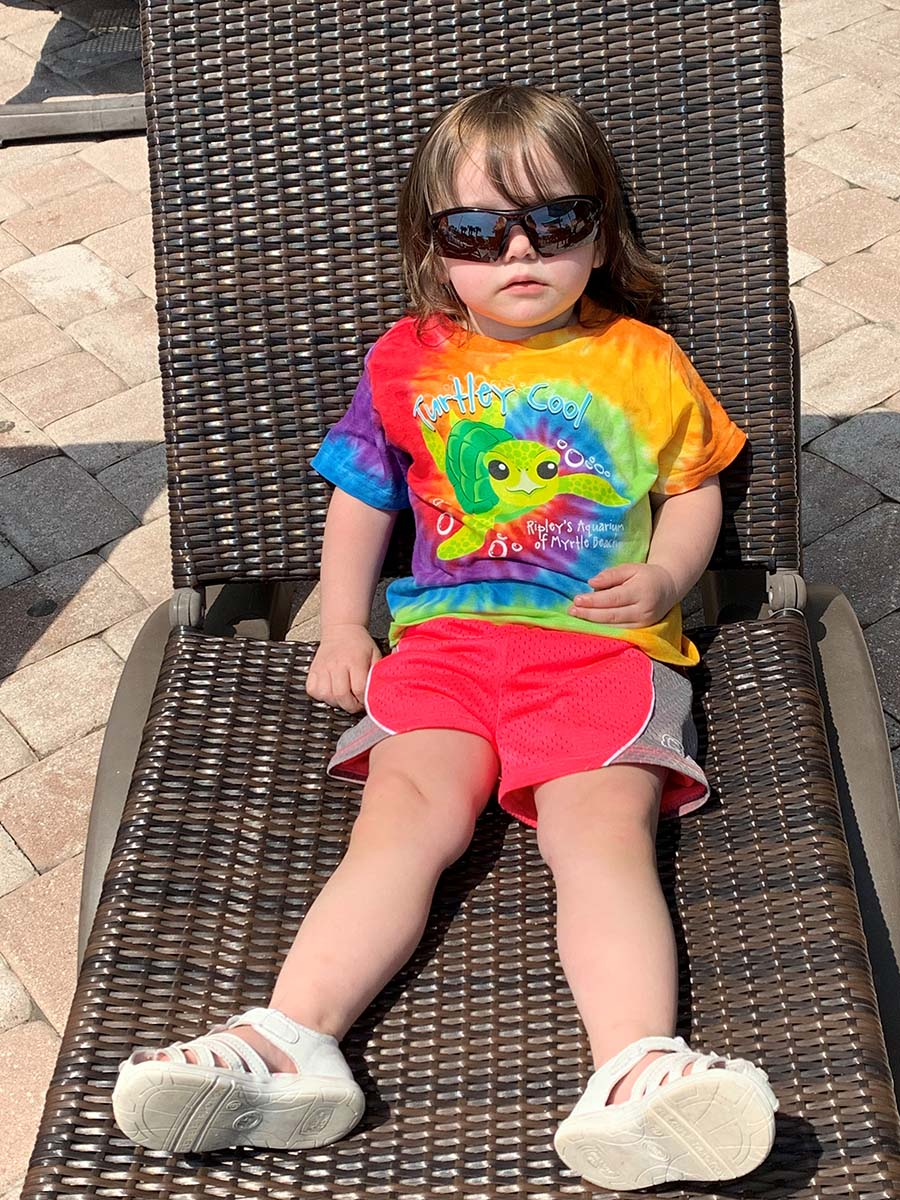 Little girl relaxing in chair on pooldeck