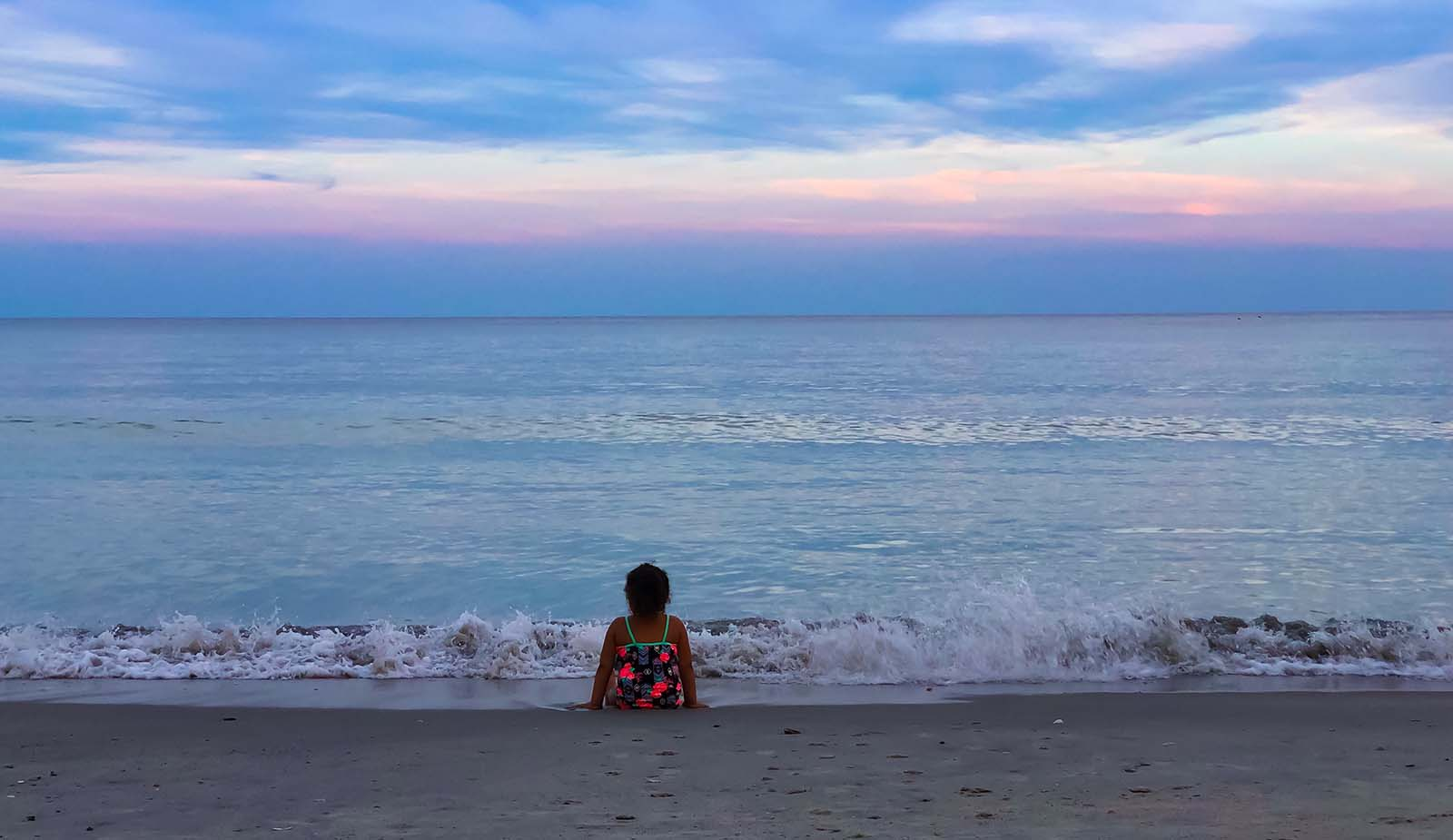 Little girl on beach at sunrise with cotton candy sky