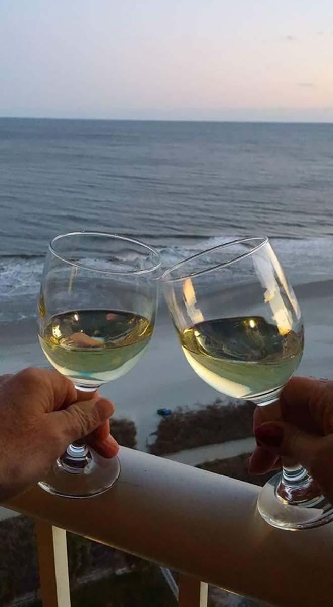 Couple drinking white wine on balcony