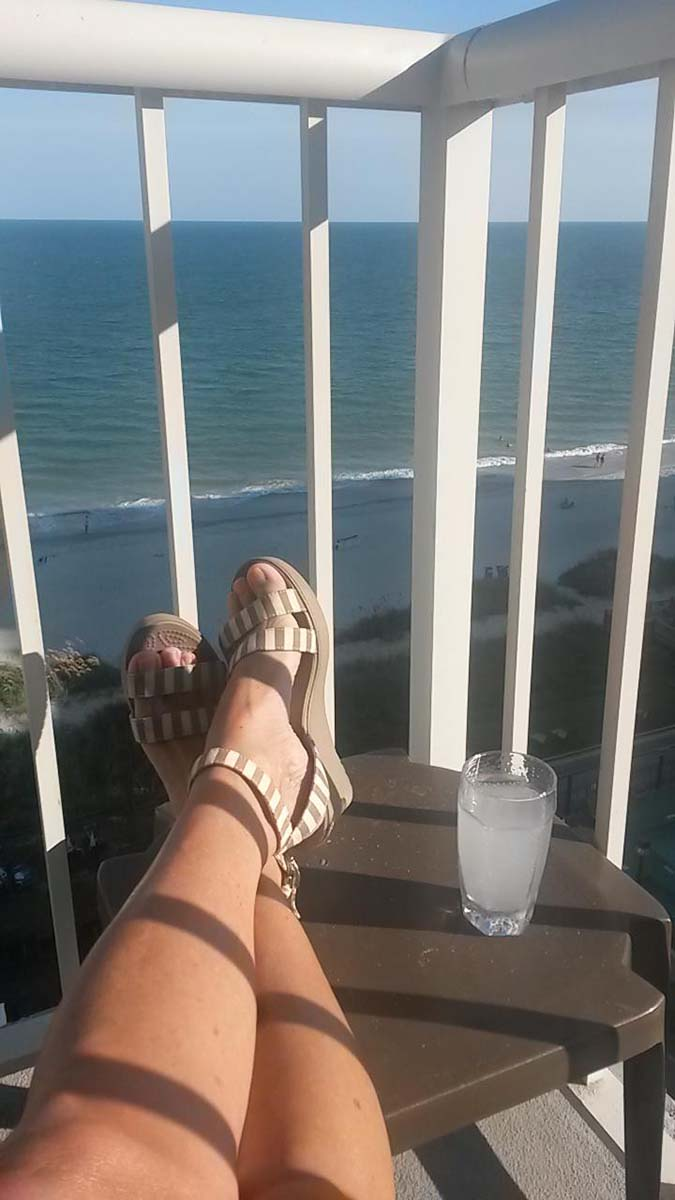 Lady with her feet up in the balcony oceanfront