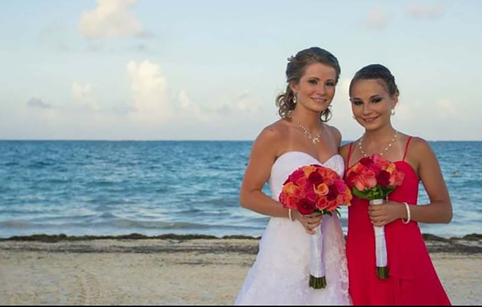 Bride and bridesmaid on beach for wedding