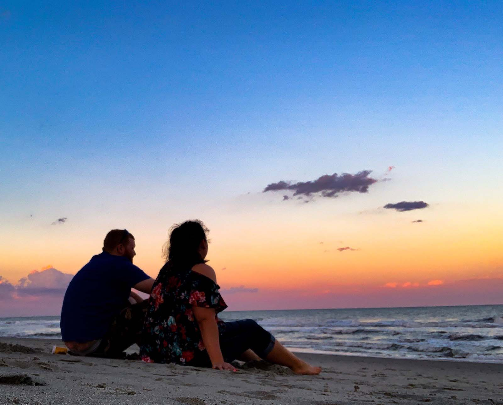 couple sitting on beach during sunset