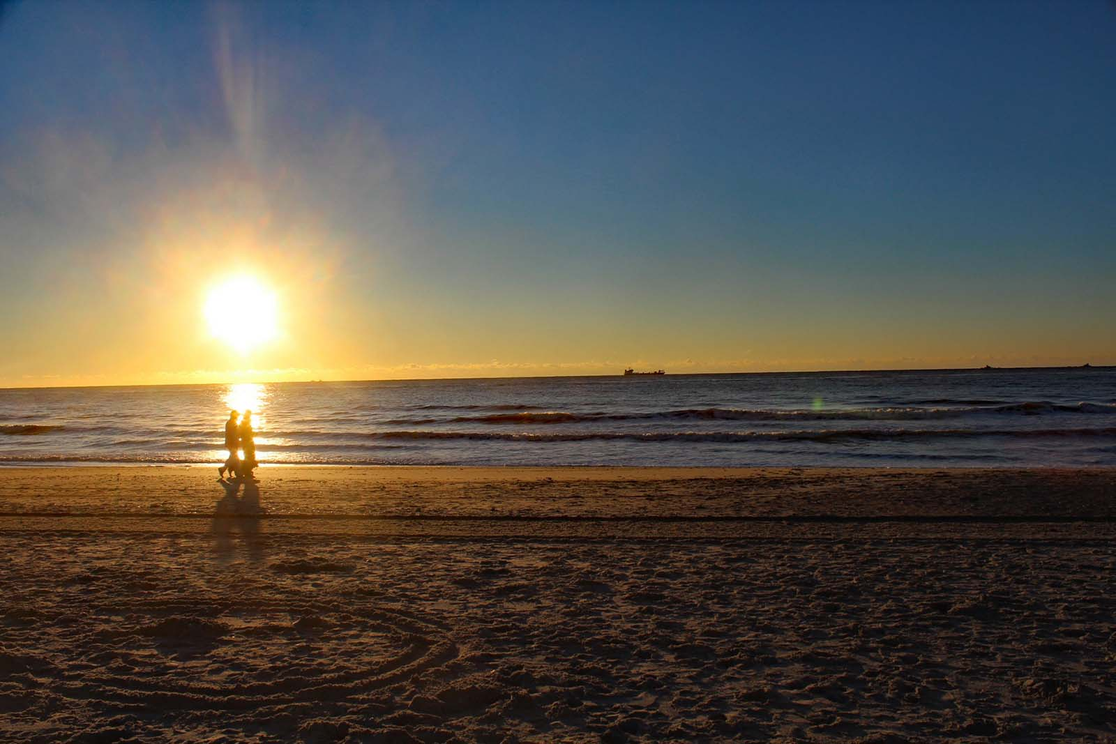 couple walking in the distance together at sunrise on the beach