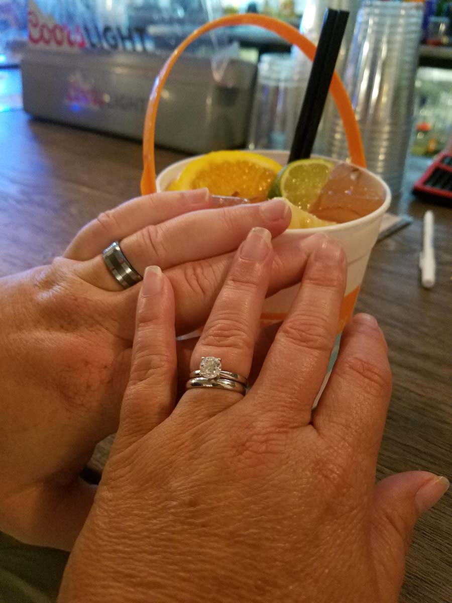 two hands with wedding rings and voodoo bucket