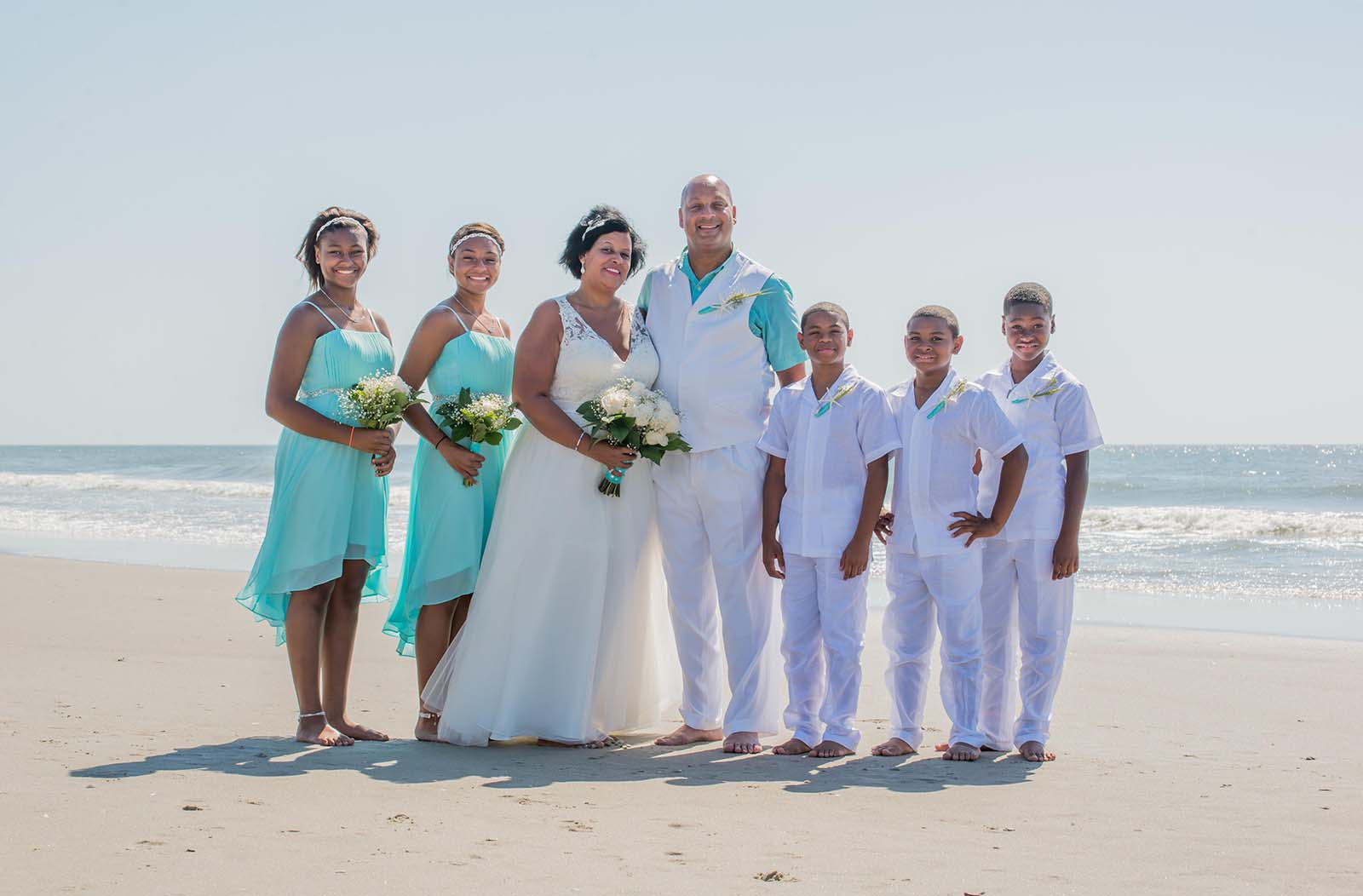 family group wedding photo in blue and white on beach
