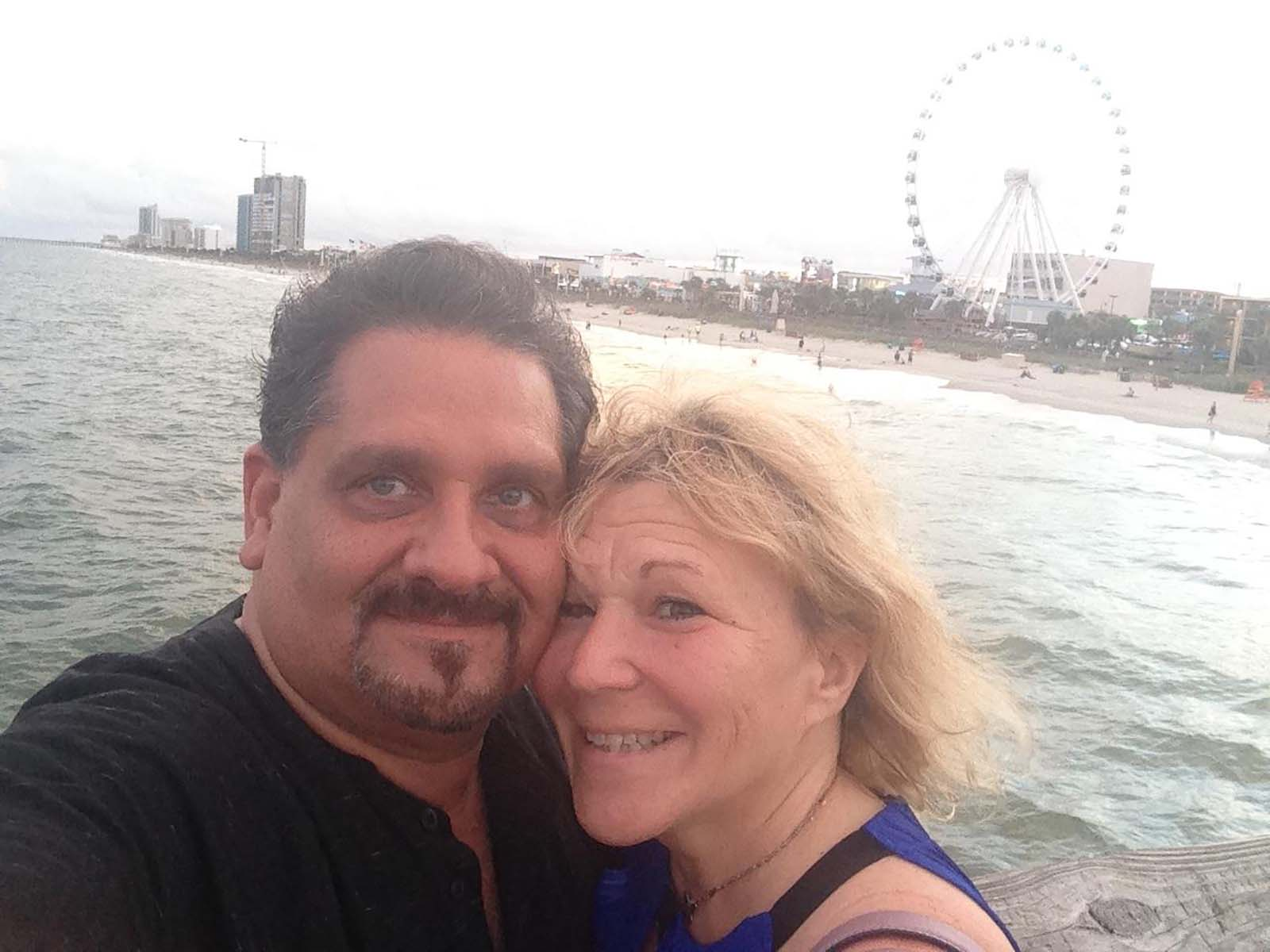 couple taking a selfie on pier with ferries wheel in the background