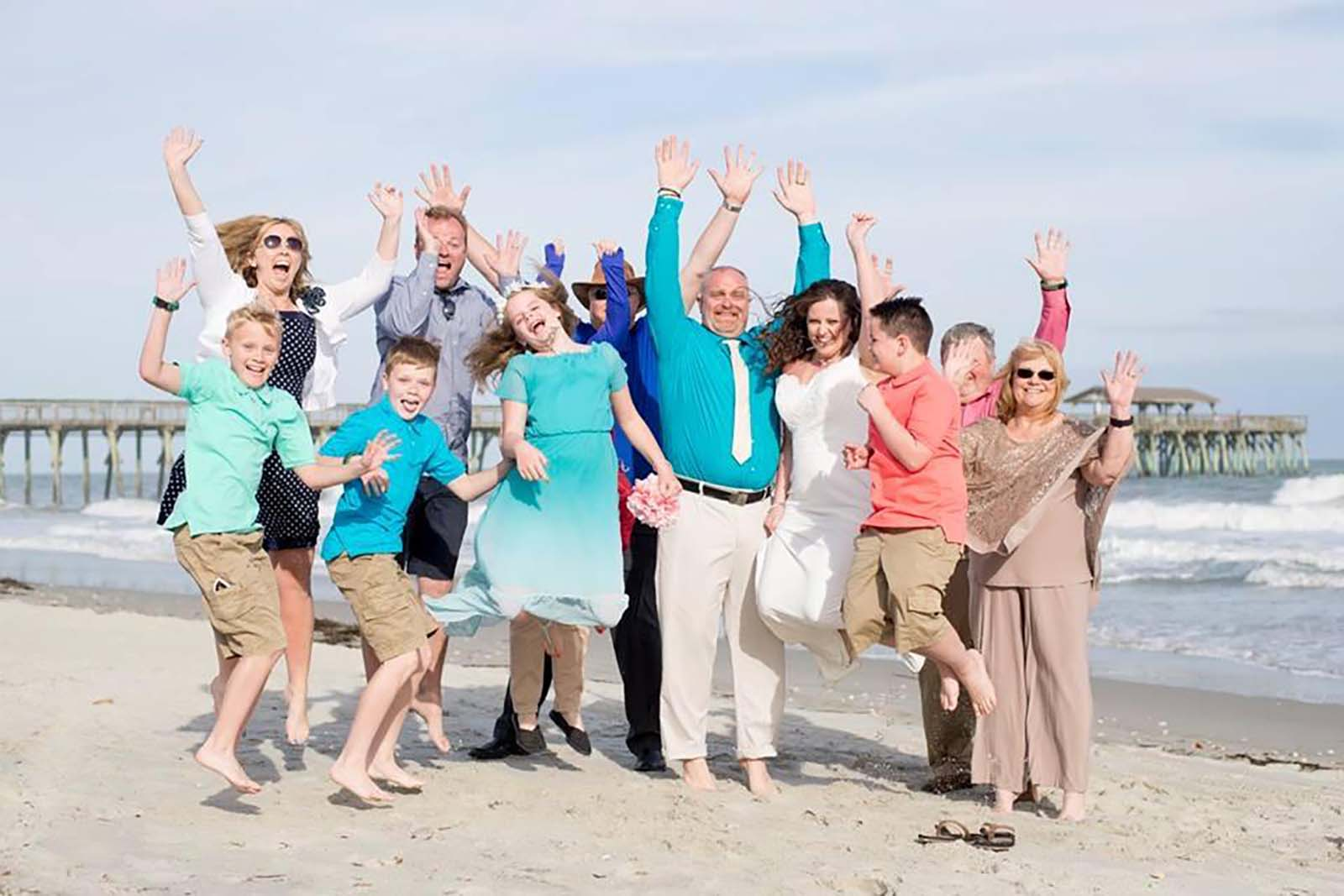 family at wedding on beach jumping