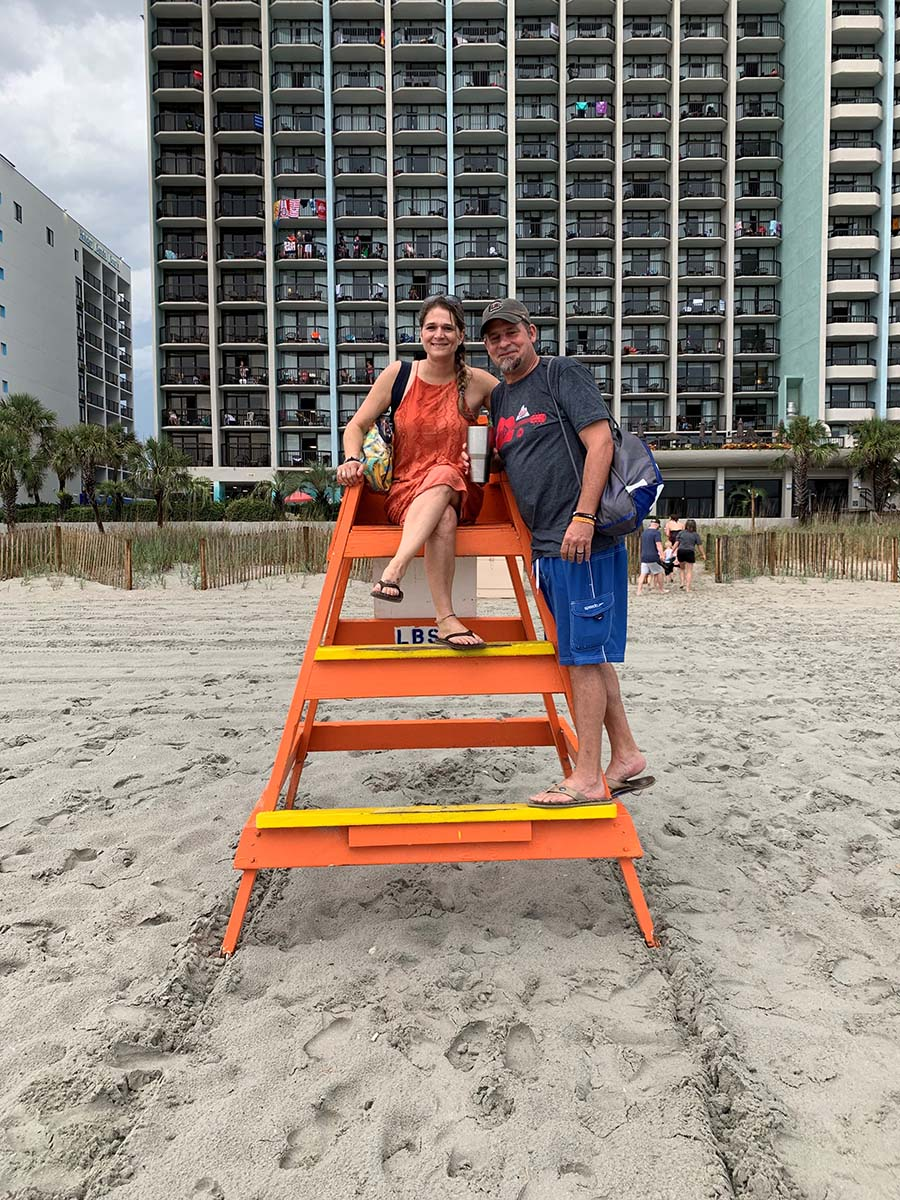 Couple sitting and posing on lifeguard stand