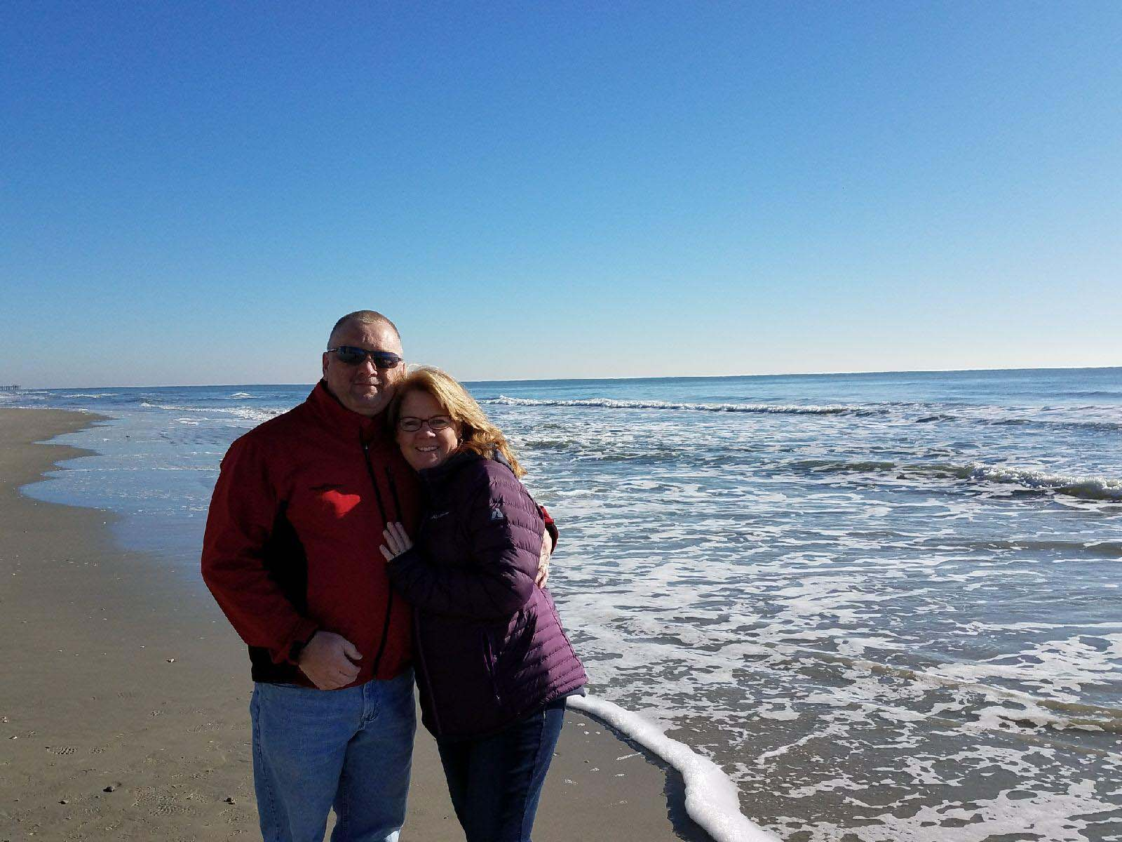 Couple hugging and posing on beach in winter
