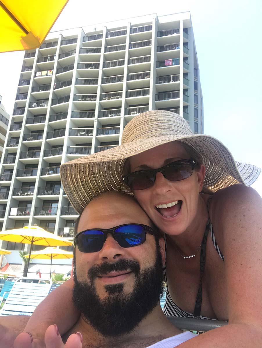 Couple taking selfie underneath yellow umbrella