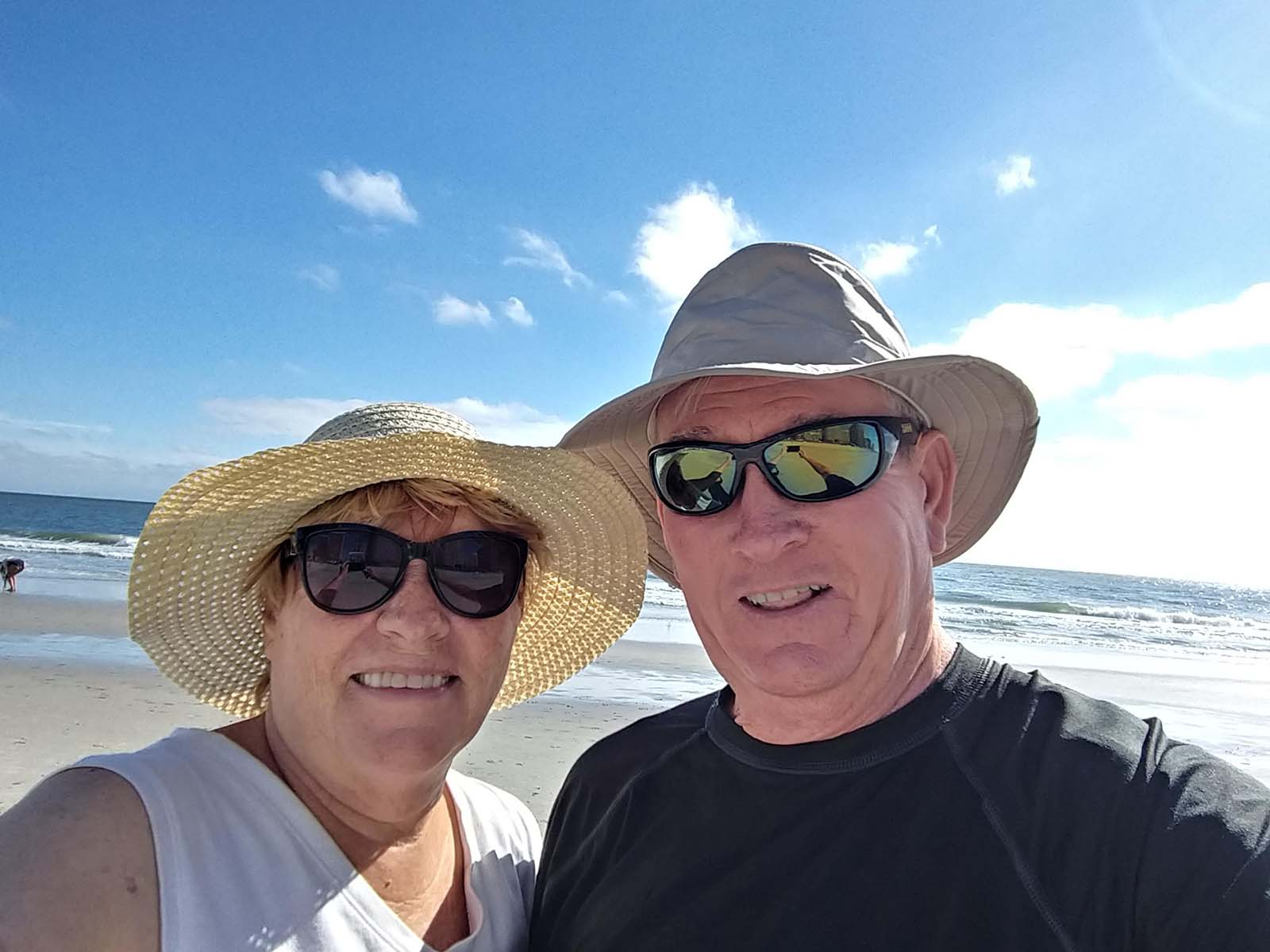Older couple in hats taking picture on beach