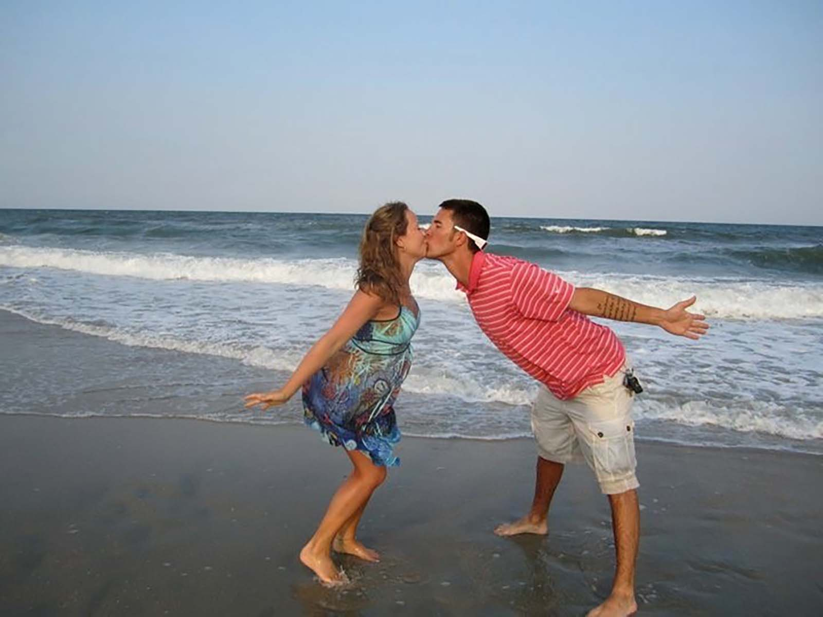 Couple on the beach kissing with hands out behind them