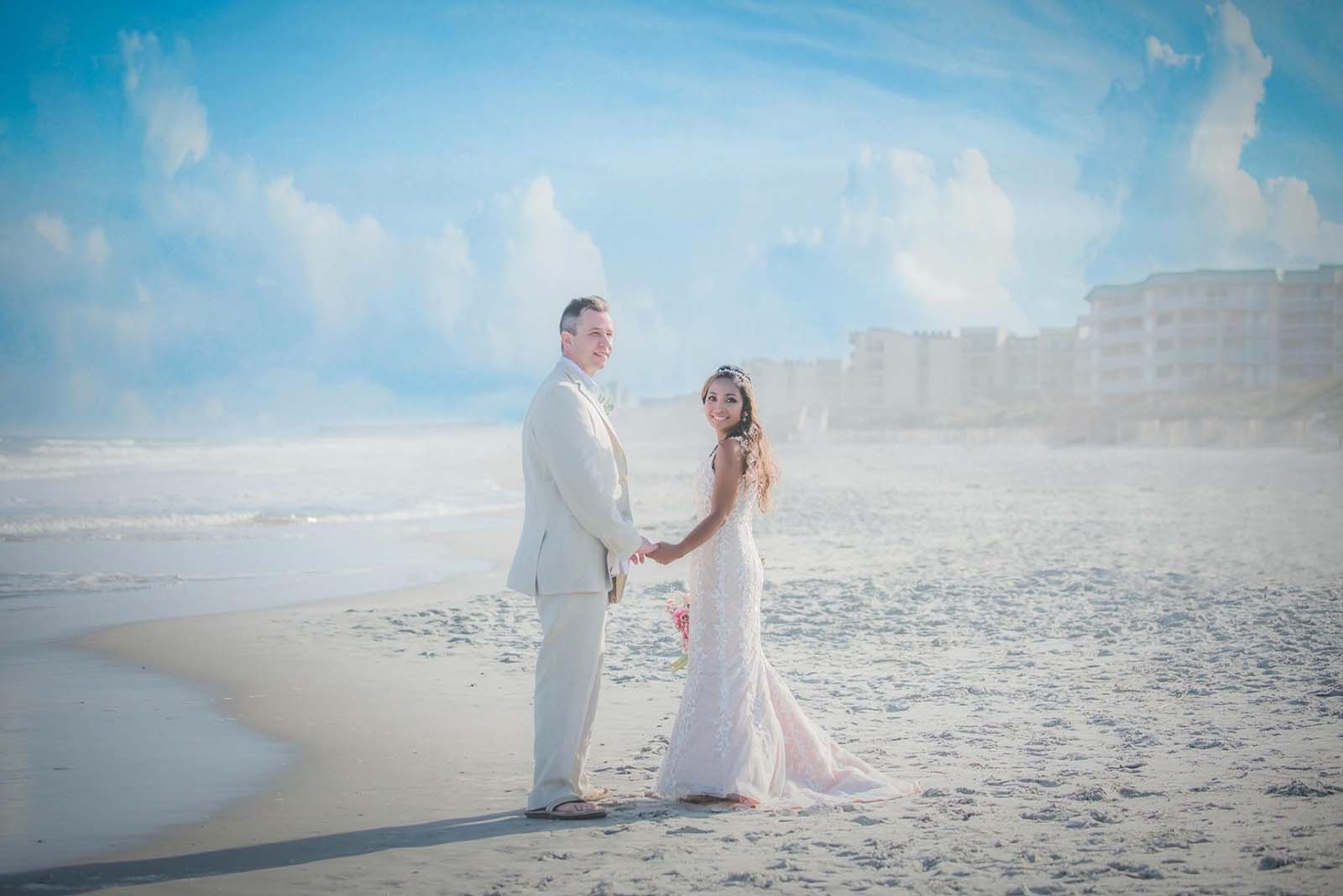 Bride and groom on beach together with blue sky