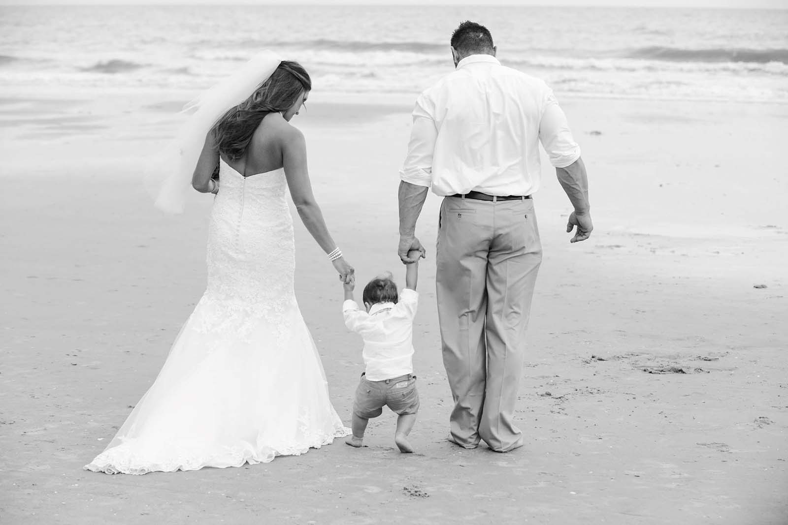 Married couple walking with baby on beach