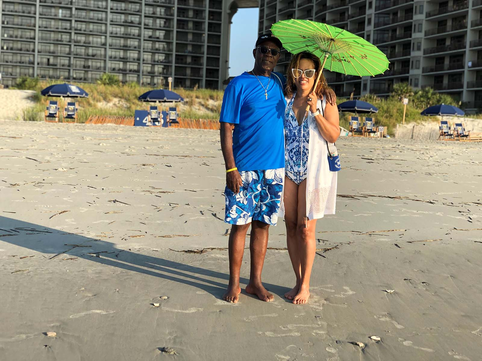 Older couple on beach with green umbrella