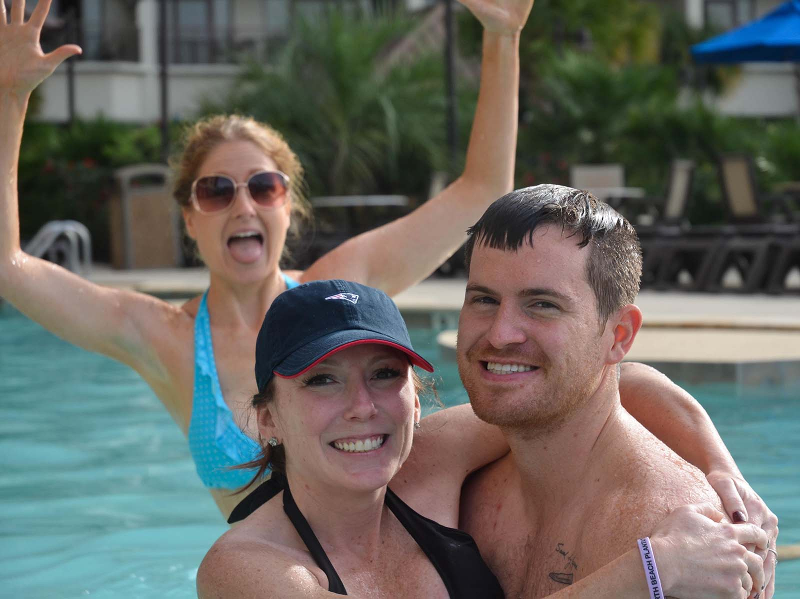 Couple selfie in pool with girl jumping in background