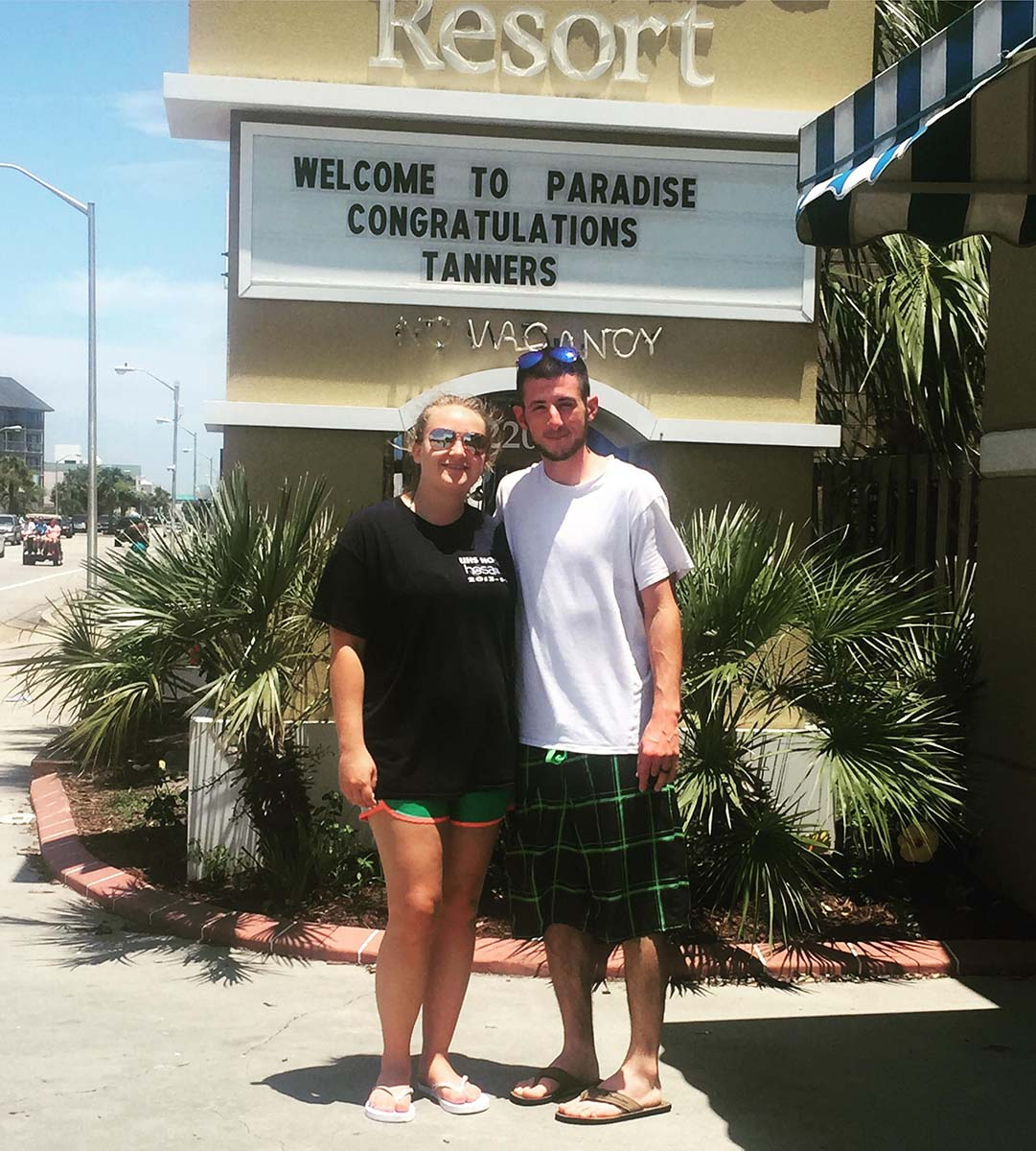 Couple picture in front of resort sign