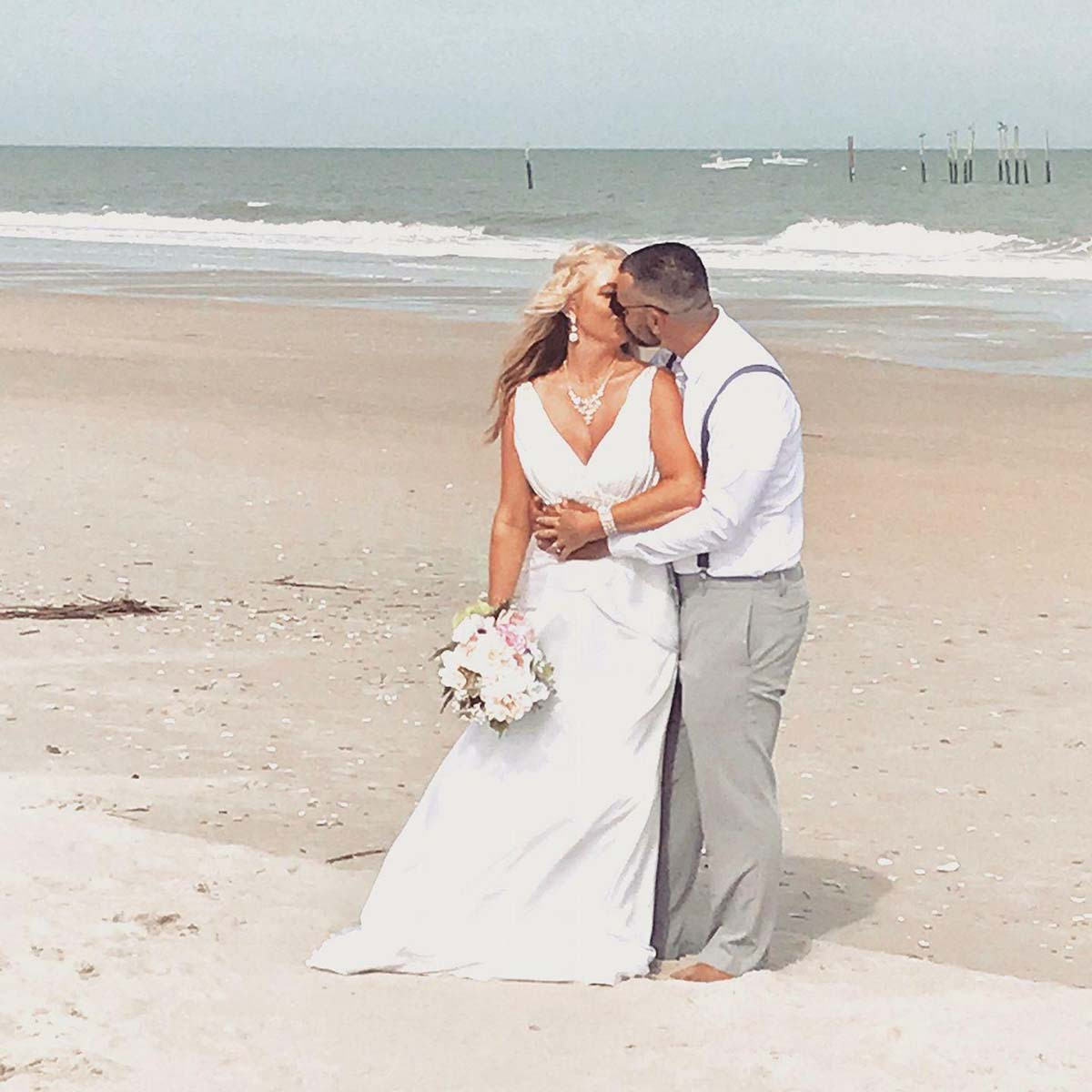 Couple kissing on the beach just got married