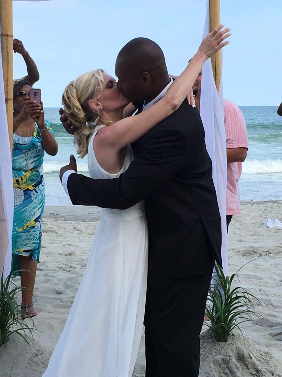 Couple getting married on bech kissing
