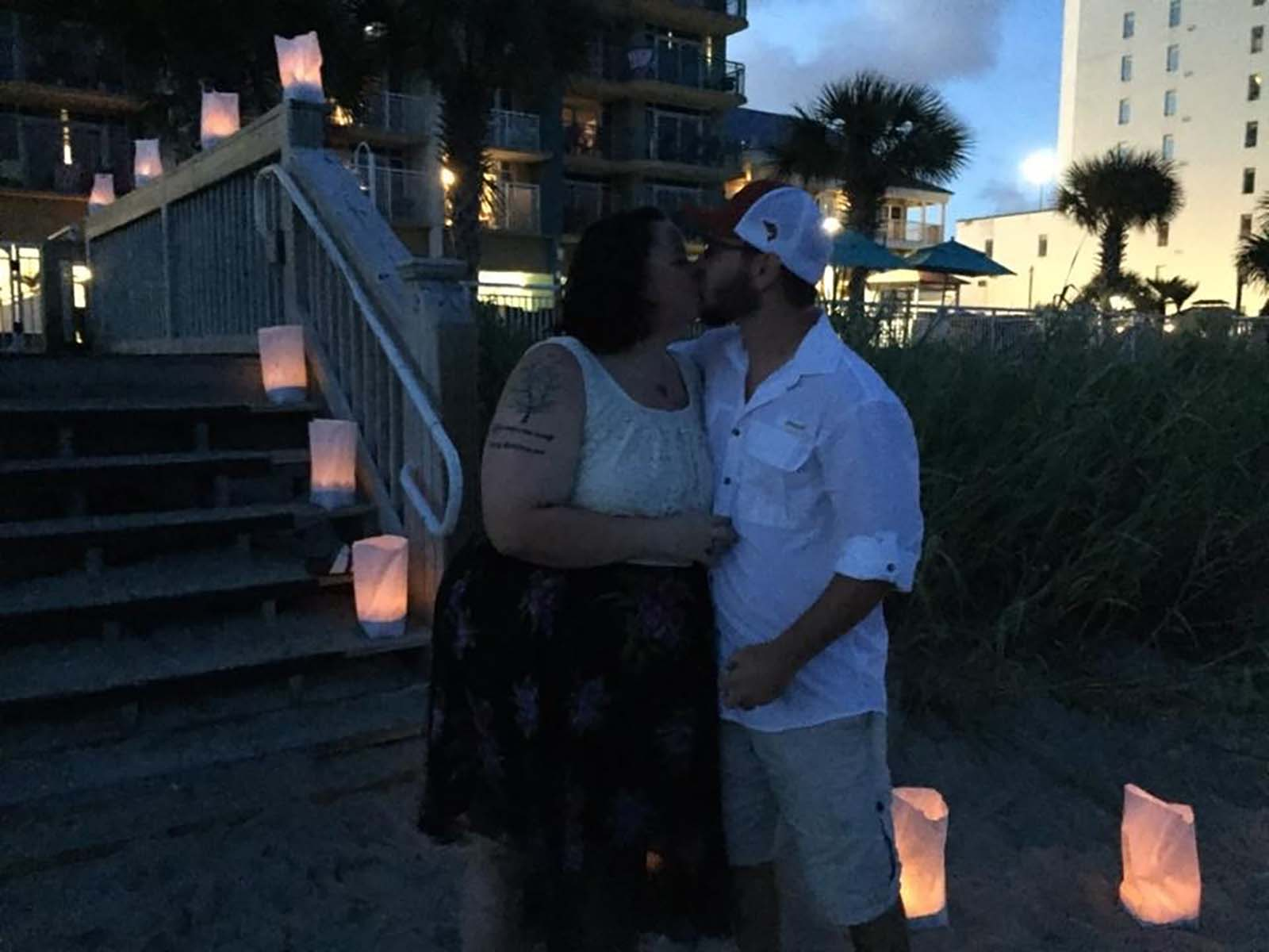 Couple kissing in the dark with lanterns