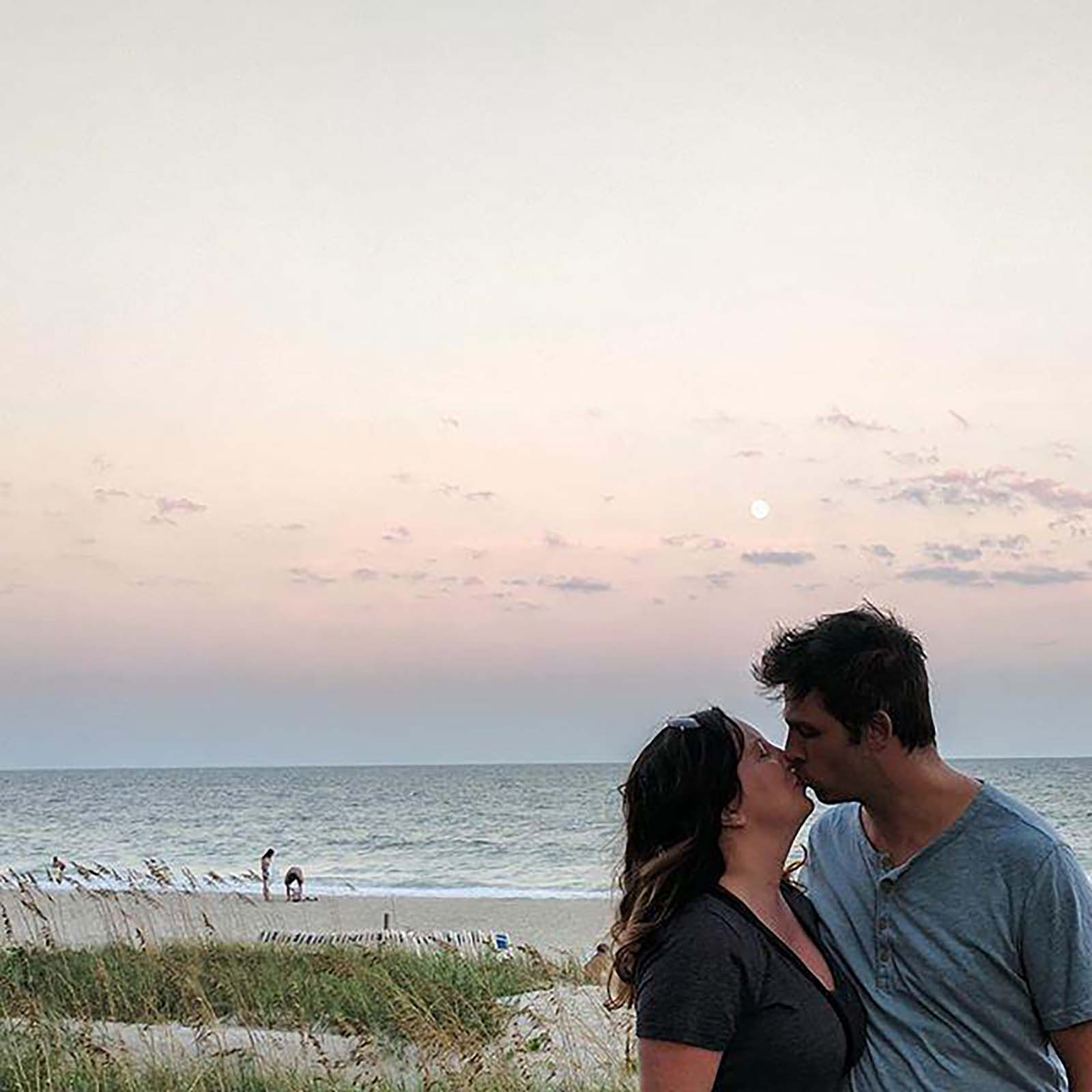 Couple Kissing on Beach with sunset in background